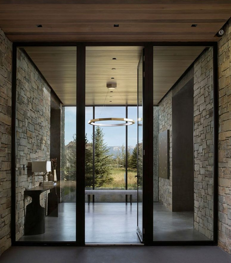 The entrance takes a full advantage of the location - its glazed wall gives a chic view