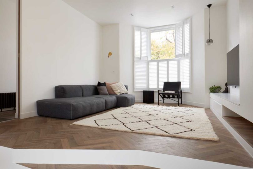 The living room itself is done with a shuttered window, a chic sofa, a printed rug and a TV on the wall