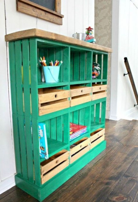 a bright emerald shelving unit built of crates and a wooden tabletop for a kids' space