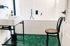 03 a neutral bathroo spruced up with dramatic black touches and an emerald tile floor with a herringbone pattern