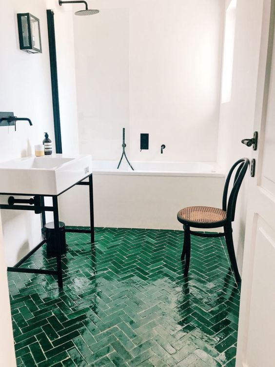 a neutral bathroo spruced up with dramatic black touches and an emerald tile floor with a herringbone pattern