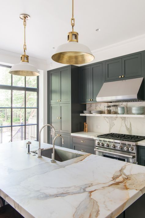 elegant white pendant lamps with gold touches accent the kitchen and echo with the gold hardware used here