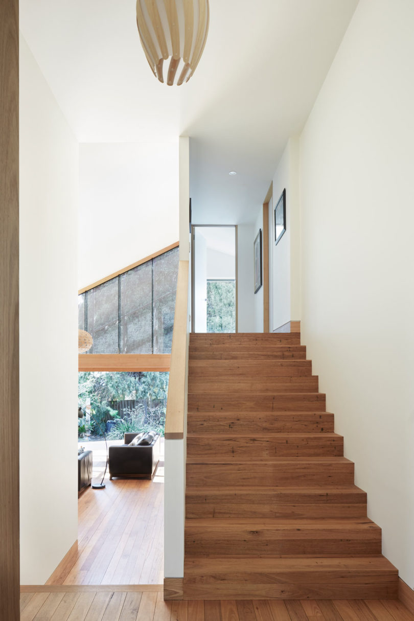 A simple wooden staircase leads upstairs to sleeping zones