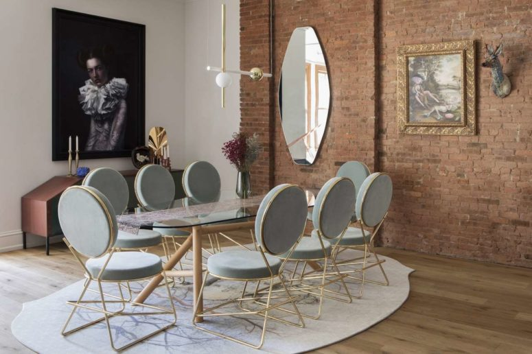The dining space is done with chic grey and gold chairs and a glass table