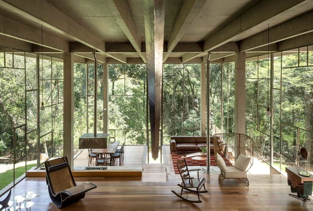 The house is done with several different spaces that are divided with glass partitions or not divided at all