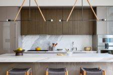 04 The kitchen is done with sleek cabinets, a marble backsplash and kitchen island and woven chairs