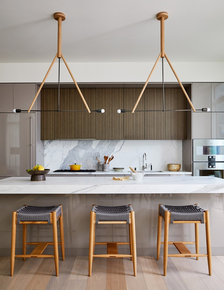 The kitchen is done with sleek cabinets, a marble backsplash and kitchen island and woven chairs