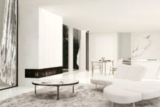 04 The living room is done with white marble, sleek white panels and stylish and simple furniture