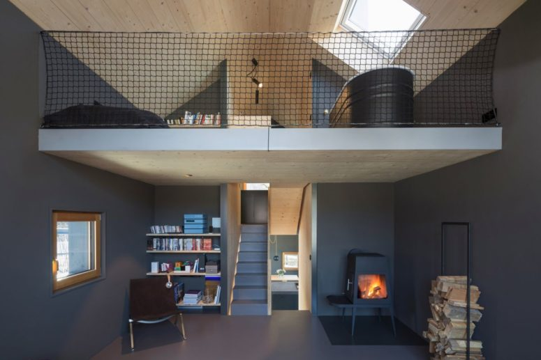 There's a living room zone with a reading nook, a hearth and a stand with firewood