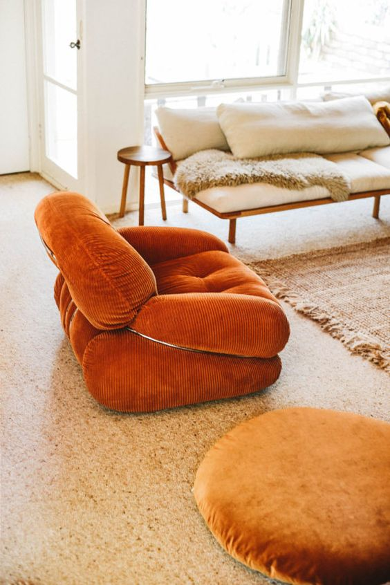 a chic rust-colored velvet chair is a stylish addiotion to a neutral and muted boho living room