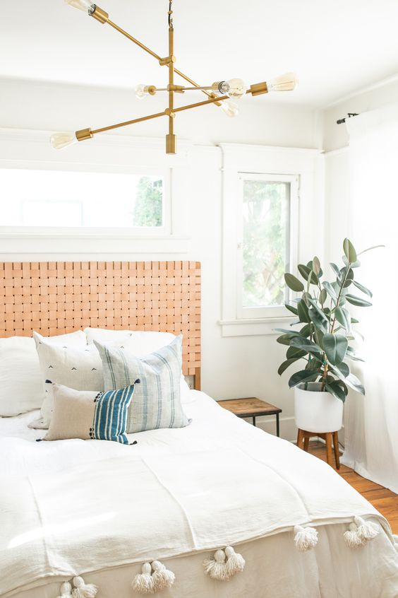 a muted orange woven leather headboard is a stylish accent for this boho bedroom that adds a warm feel to it
