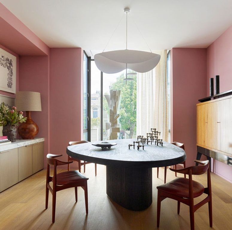A dining room with a statement wooden dining table and a gorgeous chandelier features also pink walls