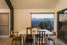 05 A square-shaped dining table with diverse chairs around it creates a very casual and friendly vibe, there's a gorgeous view