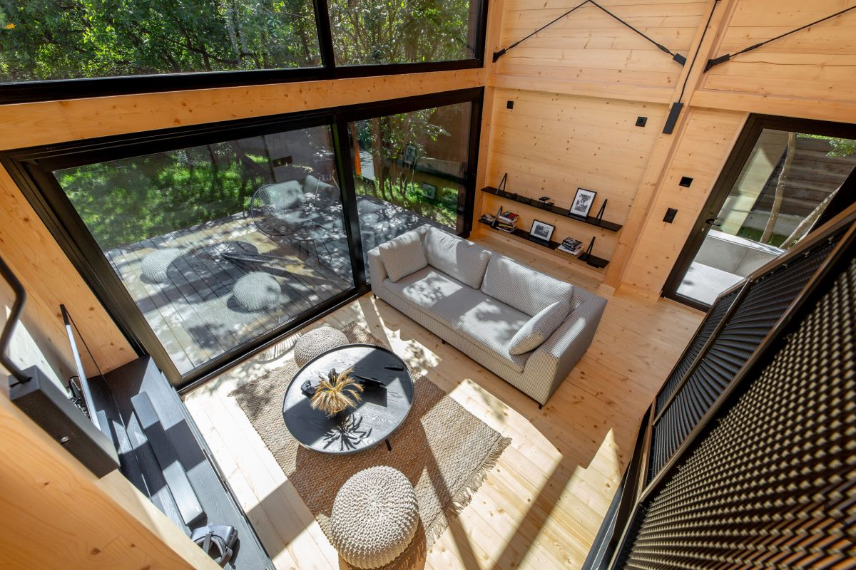 Large sliding doors open the living room towards a deck letting the owners enjoy the views and nature around