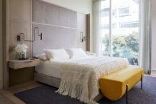 05 The bedroom is done with a floating bed, floating nightstands and a statement yellow bench of leather