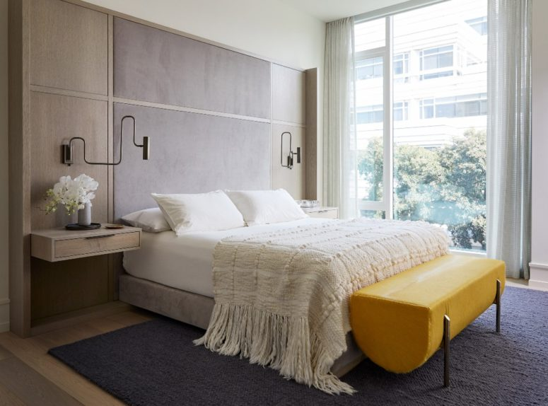 The bedroom is done with a floating bed, floating nightstands and a statement yellow bench of leather