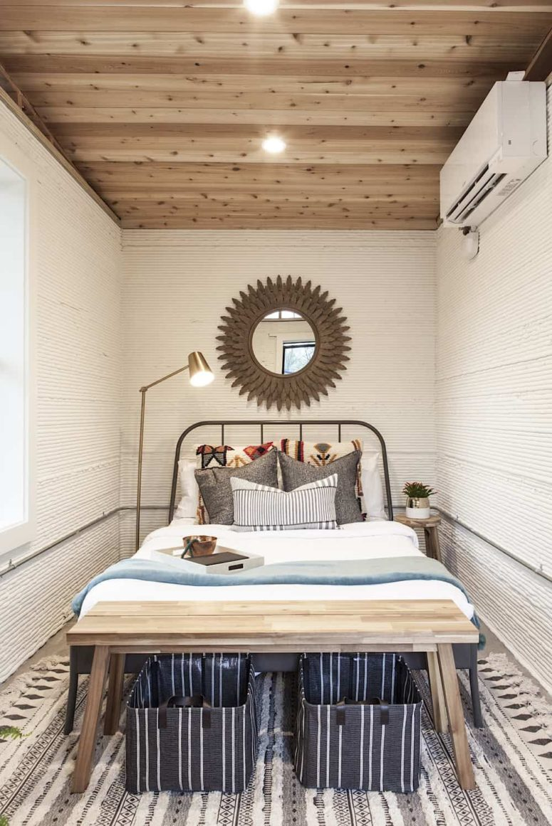 The bedroom is small yet cozy, with a metal bed, a wooden bench and a statement mirror plus a floor lamp