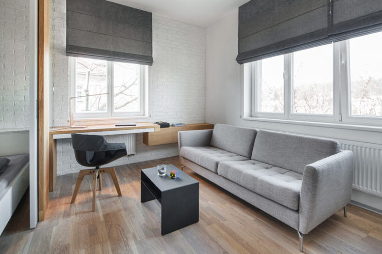 The living room features a home office nook, a comfy sofa with a coffee table and shades and there's a bedroom nok here