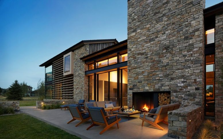 There's an outdoor living room with a fireplace, mid-century modern furniture and lights