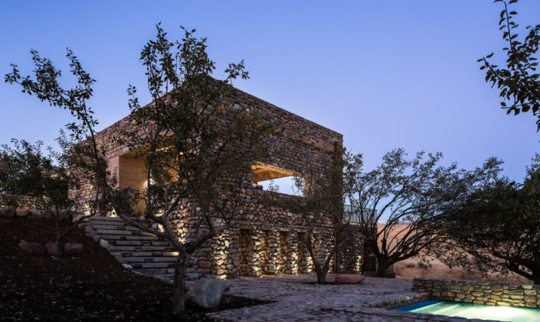 There's an outdoor space with trees, stones and a built-in swimming pool with inner lights