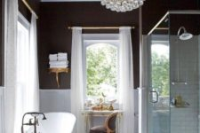 05 a gorgeous art deco bathroom with a statement crystal chandelier that adds a refined and elegant feel to the space