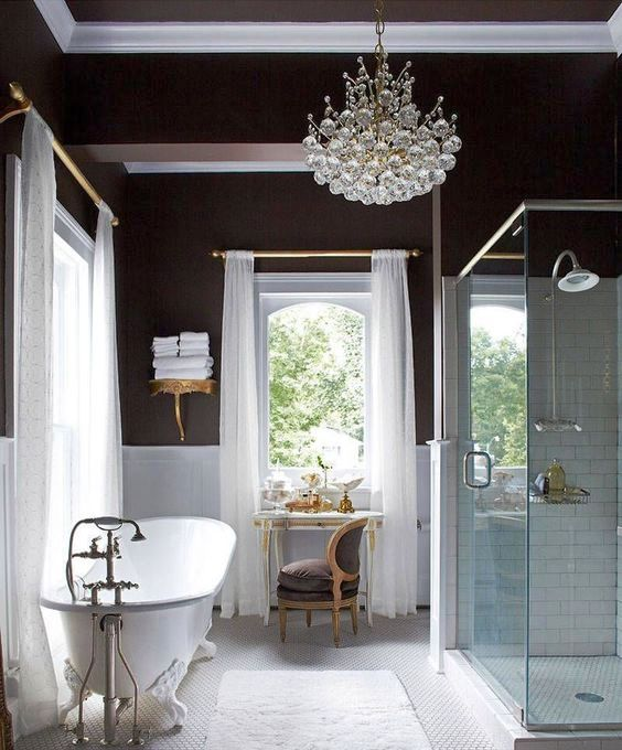 a gorgeous art deco bathroom with a statement crystal chandelier that adds a refined and elegant feel to the space