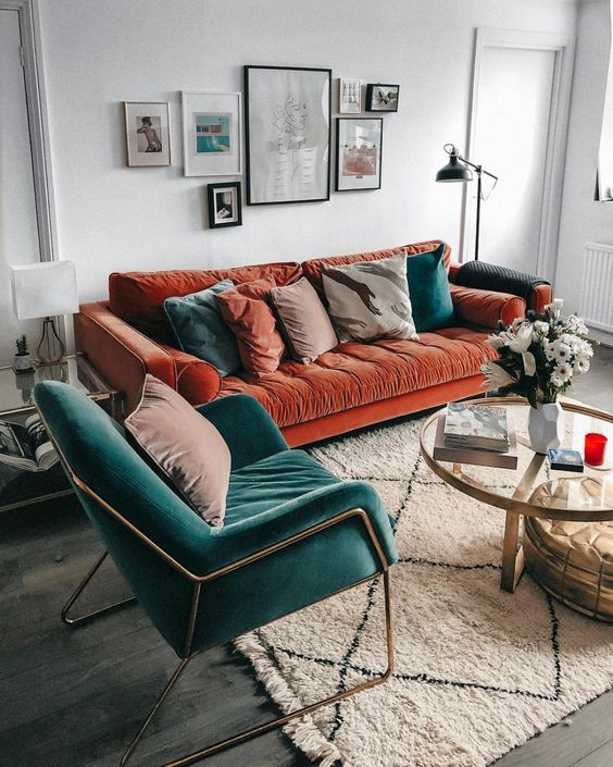 a rust colored velvet sofa with muted and teal pillows plus a teal velvet chair for a bold fall setup