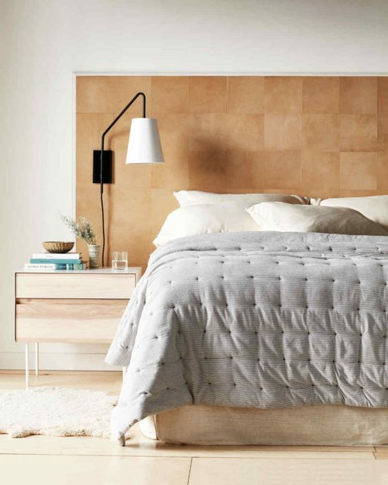 a sleek amber leather headboard with a pattern brings texture and interest to the bedroom