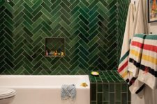 05 a statement green tile wall with a herringbone pattern and an additional green touch over the bathtub