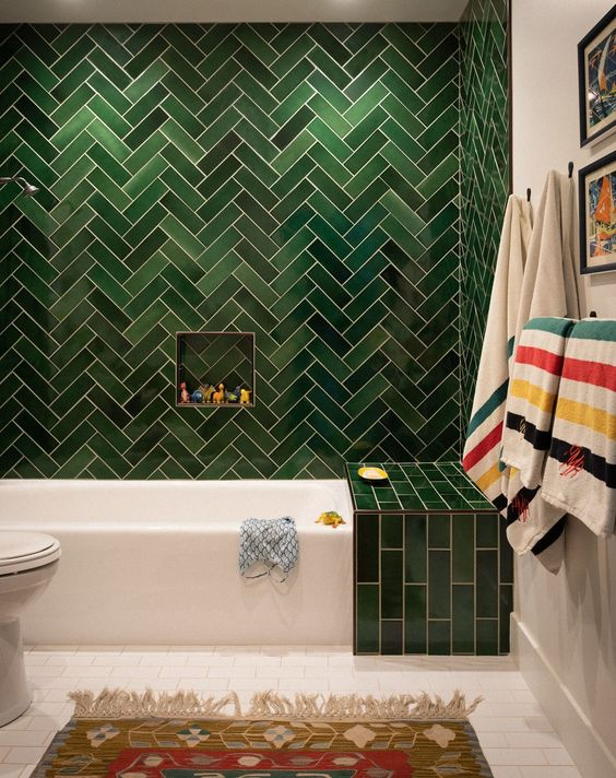 a statement green tile wall with a herringbone pattern and an additional green touch over the bathtub