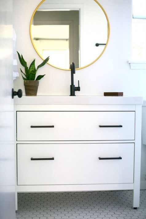 an Ikea Hemnes 2-drawer sink cabinet hacked with elegant black handles and a white countertop