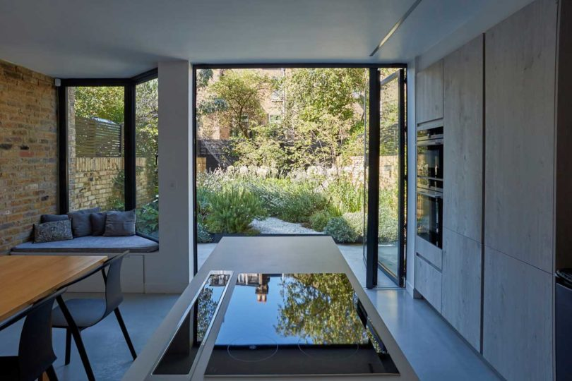 the kitchen can be opened to outdoors with a glass folding door, which leads to the garden