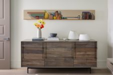 06 Catchy artworks and rustic touches like this credenza make the space more unique