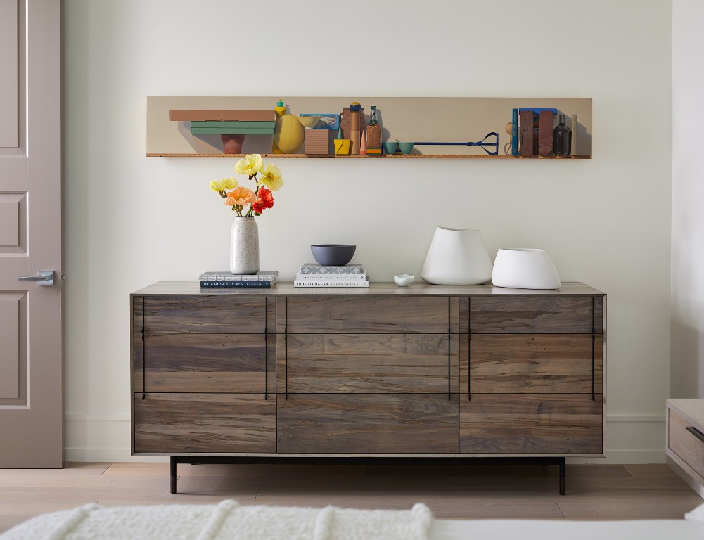 Catchy artworks and rustic touches like this credenza make the space more unique