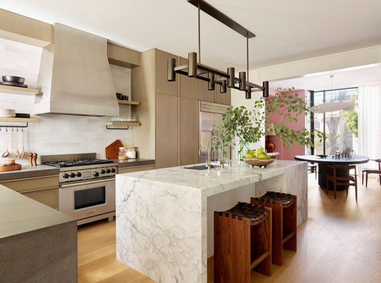 The kitchen is done with neutral plywood cabinets, a marble kitchen island and a cool track lighting fixture