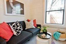 06 The living room features a black sofa, white side tables, a metal lamp and an artwork plus colorful rugs