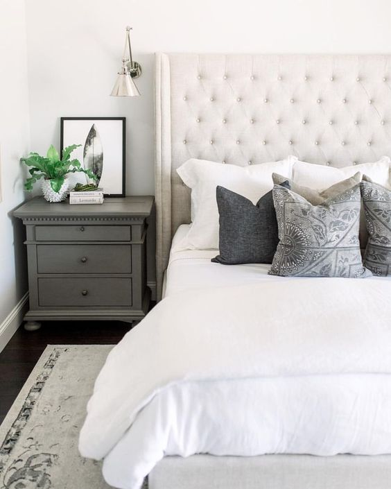 a creamy upholstered bed and a statement tall wingback headboard is a chic yet neutral enough idea for a farmhouse bedroom