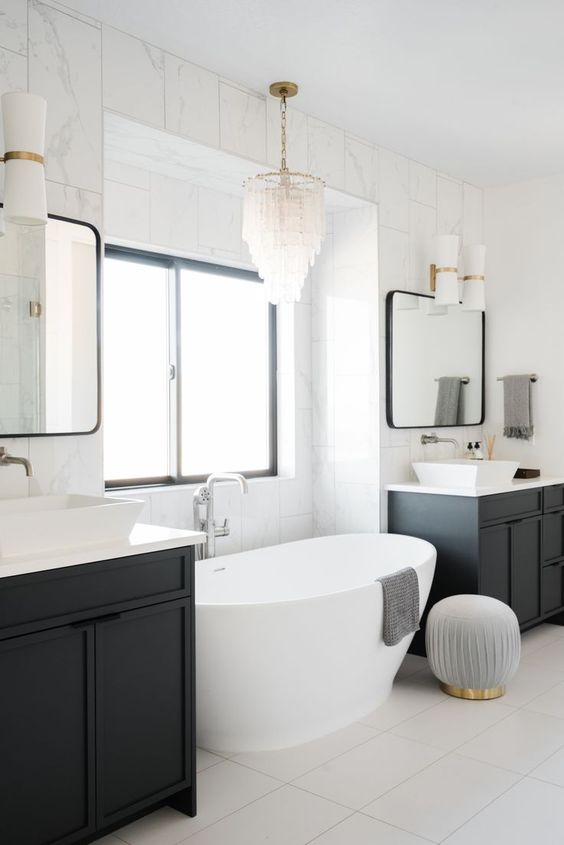 a modern take on a traditional crystal chandelier over the tub looks very cool and very chic