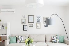 06 a small living room with a statement chandelier and a floor lamp that is used as a task light