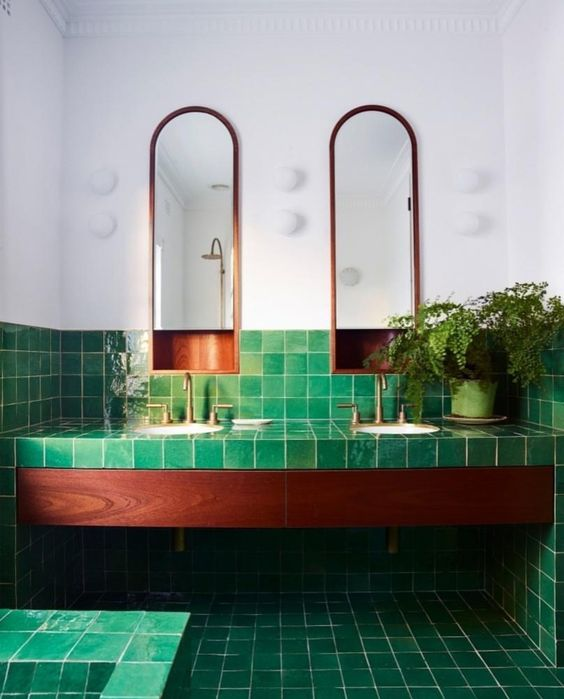 green tiles all over the bathroom contrast the rich stain of the wood and copper touches