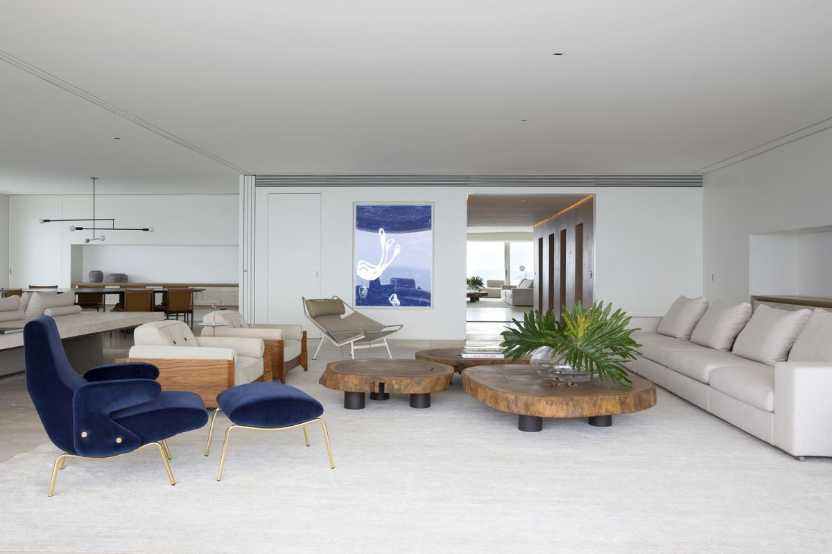 A blue statement artwork and a navy chair and footrest hint on the seaside location of the apartment