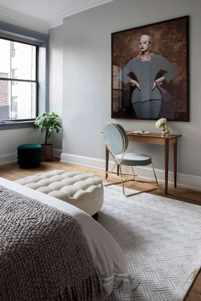 The bedroom features a statement art, a small home office space and a comfy bed