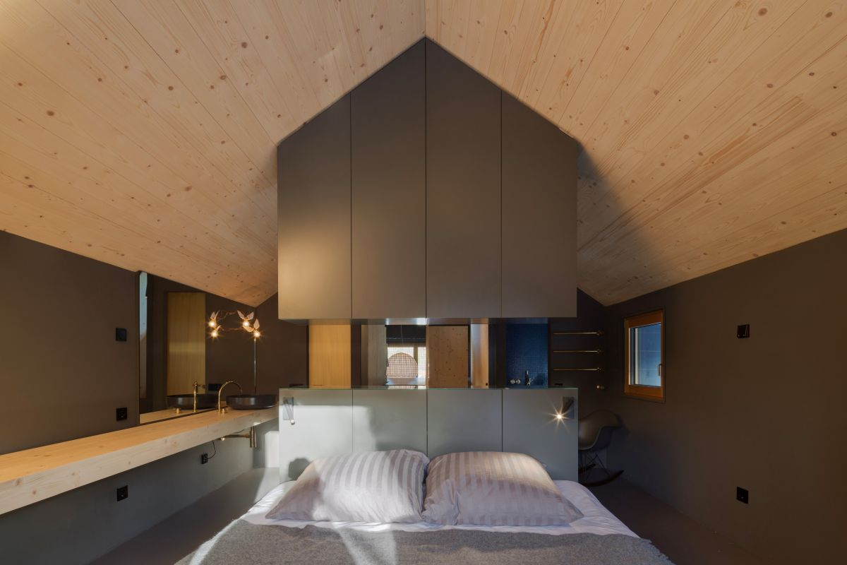 The bedroom is on the upper floor, there are lights and sleek cabinets and a bathroom integrated
