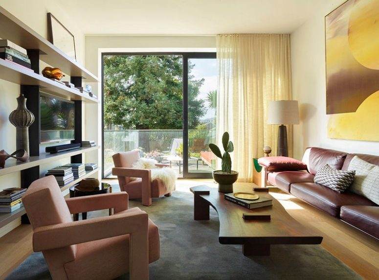 The living room is bright and bold, with pink chairs and a leather sofa plus an entrance to the terrace
