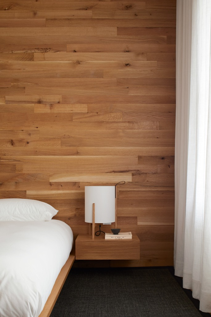 The master bedroom is done with a statement wall of wood and floating nightstands plus a floating bed, it's all neutral