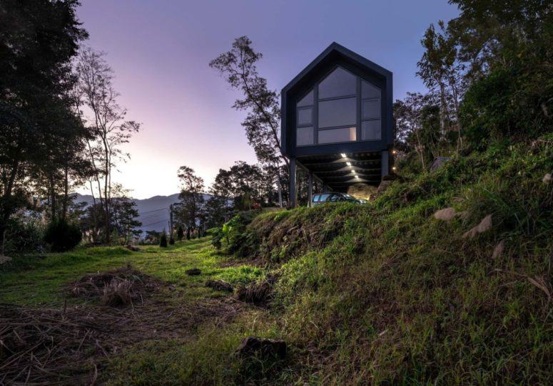 The minimalist house extends over the rugged terrain, overlooking the two valleys which frame it