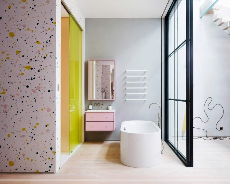 There's another bathroom done with terrazzo, pink and neon yellow touches for a bright look