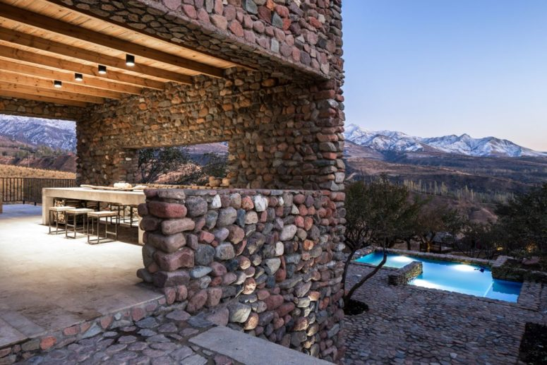 You may also see an outdoor dining space with concrete furniture and a view to the mountains