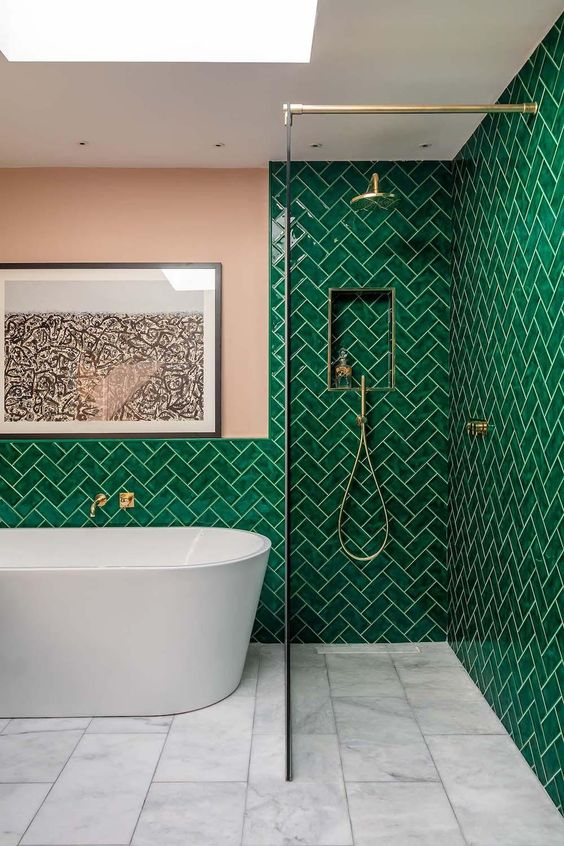 a bold bathroom with emerald tiles clad in a herringbone pattern and blush touches