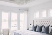 07 a creamy tufted headboard and a crystal chandelier are glam and cool accents for the space